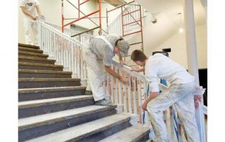 Men painting stair railing